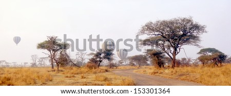 Hot air balloons above a african landscape during a safari in the serengeti - stock photo