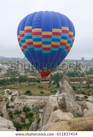 Hot air balloons (atmosphere ballons) flying over mountain landscape at Cappadocia, UNESCO World Heritage Site since 1985 - Turkey