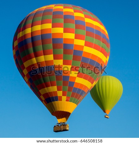 Hot air balloons flying at blue sky background - romantic landscape with two colorful balloons. Beautiful travel idea for your vacation.