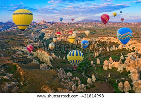 Hot air balloons flying over spectacular landscape of fairy chimneys carved in volcanic tuff by erosion. Cappadocia, Turkey - stock photo