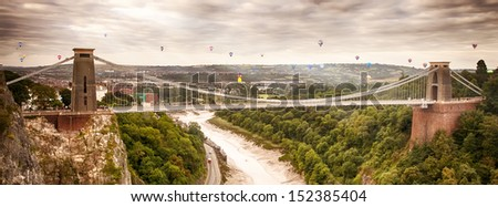 Hot air balloons in early morning lift off behind Clifton suspension bridge - stock photo