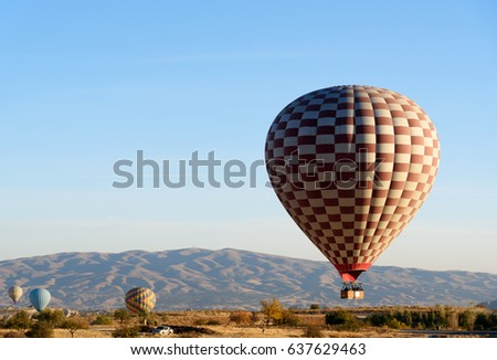 Hot air balloons landing after flight over valley of Cappadocia in the morning. Nevsehir Province. Turkey.