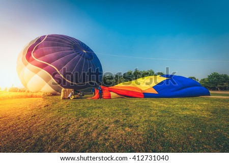 Hot air balloons on green field in sun rise - stock photo