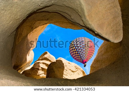 Hot air balloons over mountain landscape in Cappadocia, Goreme National Park, Turkey.