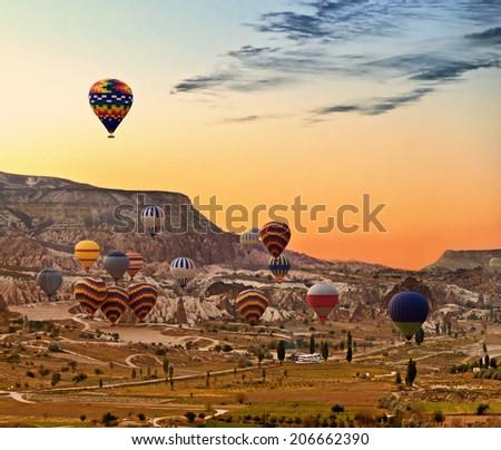 Hot air balloons over the limestone ridge in Caapadocia, Turkey. - stock photo