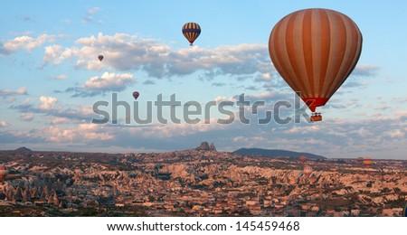 Hot air balloons rise over Goreme town in Cappadocia, Turkey - stock photo