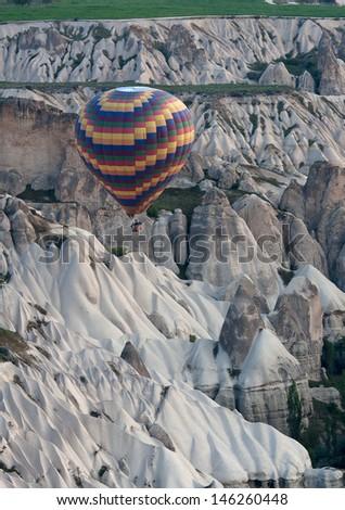 Hot air balloons rise over valley in Cappadocia, Turkey - stock photo