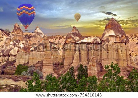 Hot air balloons sunset discovery Love valley in Goreme nationa park, rock valley landscape, Cappadocia, Turkey