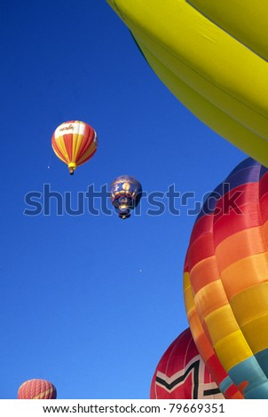 Hot Air Balloons Together Vertical Composition Flying in Balloon Festival Blue Sky Calm Day New Mexico - stock photo