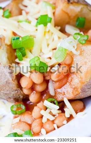 Hot and crispy baked potato stuffed with baked beans, cheddar cheese and sliced spring onions - stock photo