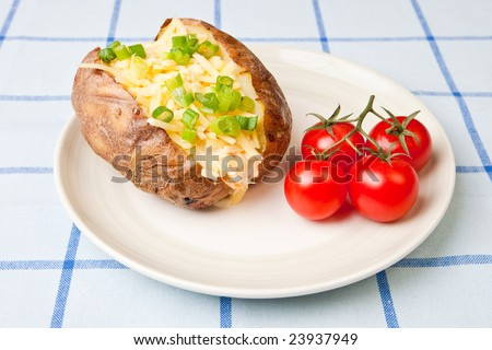 Hot and crispy baked potato stuffed with cheddar cheese, coleslaw and tomatoes - stock photo