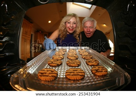 Hot and Fresh COOKIES right from the oven!  A lady bakes cookies for a charity bake sale to help raise money for a Homeless Cats. - stock photo
