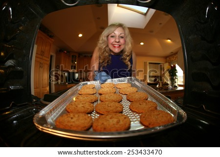 Hot and Fresh COOKIES right from the oven!  A lady bakes cookies for a charity bake sale to help raise money for a Wounded Solders. - stock photo