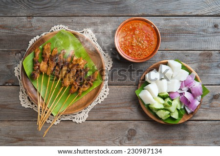 Hot and spicy Asian dish. Chicken sate or satay, skewered and grilled meat, served with peanut sauce. Fresh cooked with steamed and smoke.  - stock photo