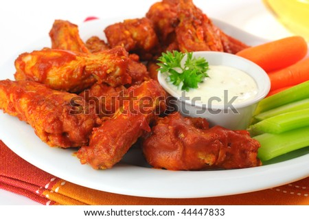 Hot and spicy buffalo chicken wings with fresh vegetables. - stock photo