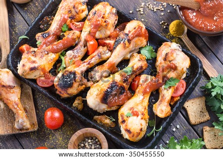 Hot and spicy chicken drumsticks on serving pan. Toned - stock photo