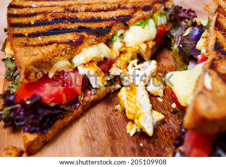 Hot and spicy club sandwich with chicken, tomatoes, mozzarella, basil, lettuce, chilli - stock photo