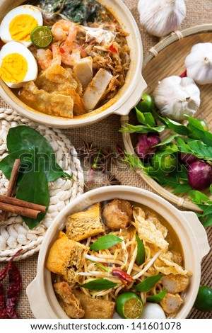 Hot and spicy Curry Noodles or laksa  mee and prawn noodle with hot steam in clay pot, decoration setup, serve with chopsticks. Asia cuisine. - stock photo
