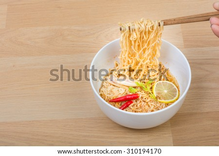 Hot and spicy lap instant noodle on wooden background - stock photo
