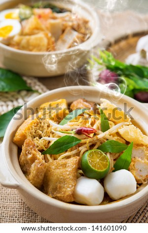 Hot and spicy Malaysian Curry Noodles or laksa  mee with hot steam in clay pot, decoration setup, serve with chopsticks. Malaysia cuisine. - stock photo