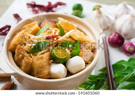Hot and spicy Singapore Curry Noodle or laksa  mee with hot steam in clay pot, decoration setup, serve with chopsticks. Singaporean cuisine. - stock photo