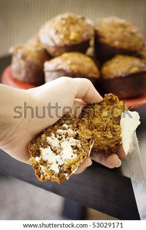 Hot Apple Bran Muffins Being Buttered - stock photo