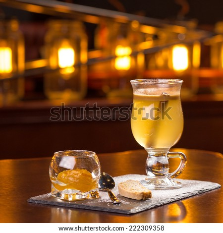 Hot apple cider served with jam and cookie on the bar - stock photo