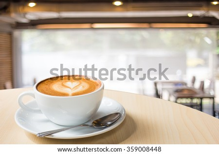 Hot art Latte Coffee in a cup on wooden table and Coffee shop blur background with bokeh image - stock photo
