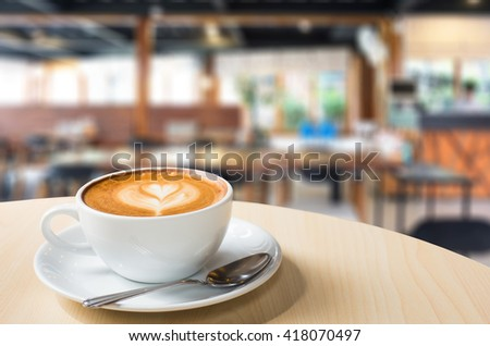 Hot art Latte Coffee in a cup on wooden table and Coffee shop blur background with bokeh image.