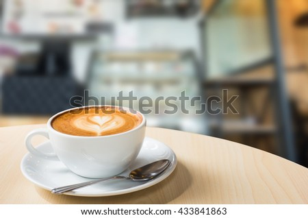 Hot art Latte Coffee in a cup on wooden table and Coffee shop blur background with bokeh image