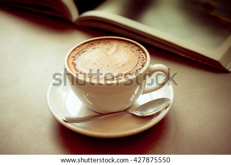 Hot art Latte Coffee in a cup on wooden table with book