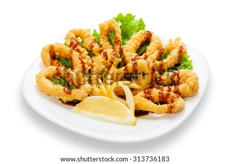 Hot asian restaurant snack - deep fried calamari rings with lemon served on a white square plate isolated at white background