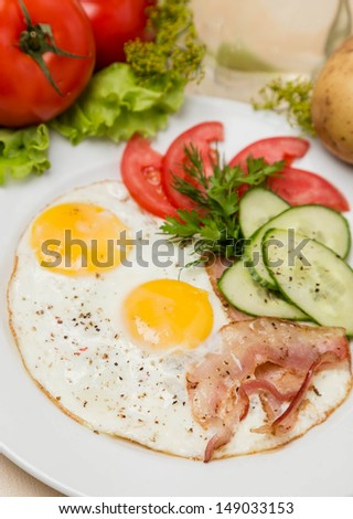 hot bacon and eggs with garnish on white plate