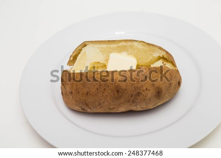 Hot baked potato on a white plate with butter - stock photo