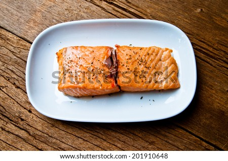 Hot baked Salmon Fillet Piece Served Over White Plate on Wood Table Background, Delicious Healthy food, Country Rustic Style. - stock photo