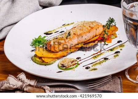 hot baked salmon with vegetables on glass plate isolated. Restaurant
