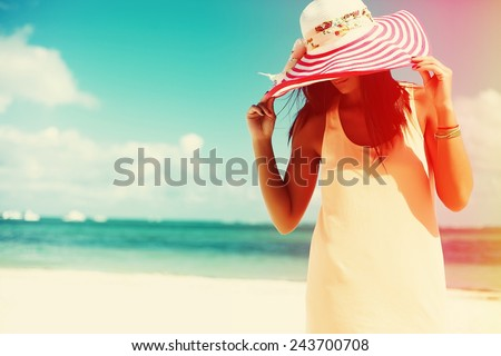 Hot beautiful woman in colorful sunhat and dress walking near beach ocean on hot summer day on white sand - stock photo