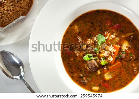 Hot Beef Goulash Soup. Garnished with Bread - stock photo
