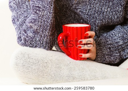 Hot beverage. Closeup female hand holding red cup mug hot drink tea or coffee, sitting on couch. Woman in warm sweater warming herself - stock photo