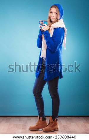 Hot beverage. Full length teen girl holding blue mug with drink tea or coffee. Woman warming herself studio shot - stock photo