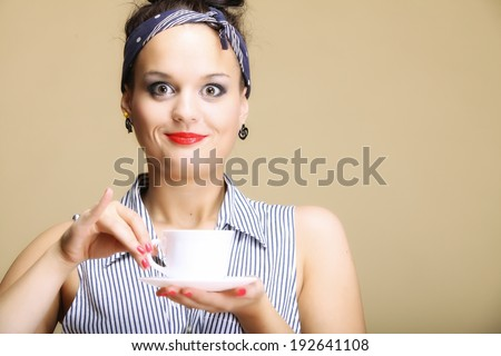 Hot beverage. Woman funny girl holding a cup of tea or coffee copyspace brown background - stock photo
