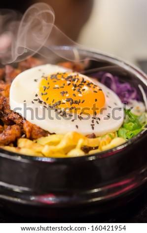 hot bibimbap in a heated stone bowl ,  korean style food - stock photo