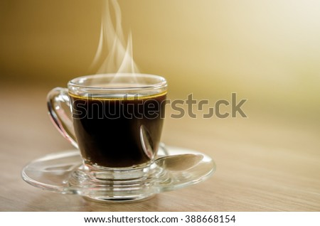 Hot black coffee in glass cup with smoke on wooden table. - stock photo