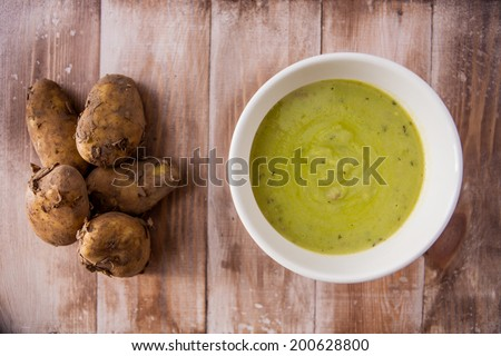 Hot bowl of pea soup with raw new potatoes on a rustic wooden background