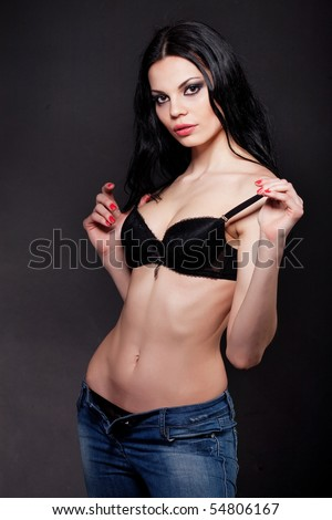 Hot brunette in lingerie and jeans isolated on black - stock photo