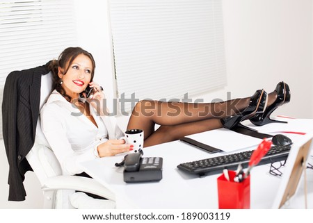 hot office pic. Hot Business Woman Sitting In The Office With Legs On Table And Talking Mobile Pic