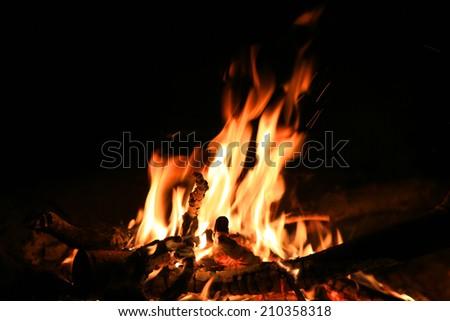 Hot camp fire in dark night  - stock photo