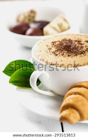 Hot cappuccino and pastries on white wooden boards