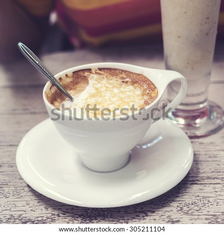 Hot cappuccino coffee in white cup on wodd background, vintage color tone. - stock photo