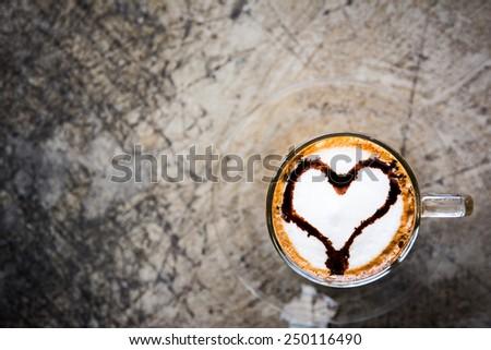 Hot cappuccino coffee with chocolate heart shape on foam  - stock photo